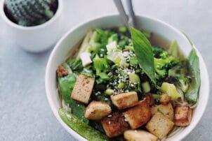 grüne Salatbowl mit Fleischersatz und Baguettestückchen getoppt / snackconnection