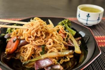 japanische Bratnudeln auf einem Teller mit Gemüse / snackconnection
