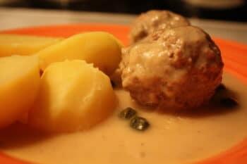 Königsberger Klopse mit Kartoffeln und Soße auf einem Teller / snackconnection