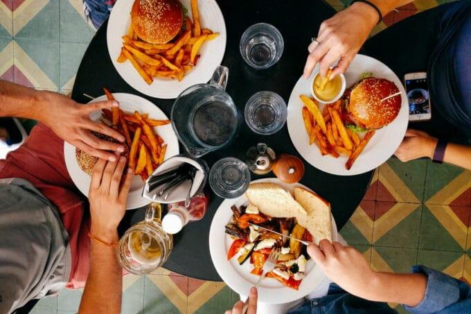 Tisch mit Pommes, Burgern, Sandwich und Gemüse von oben fotografiert / snackconnection