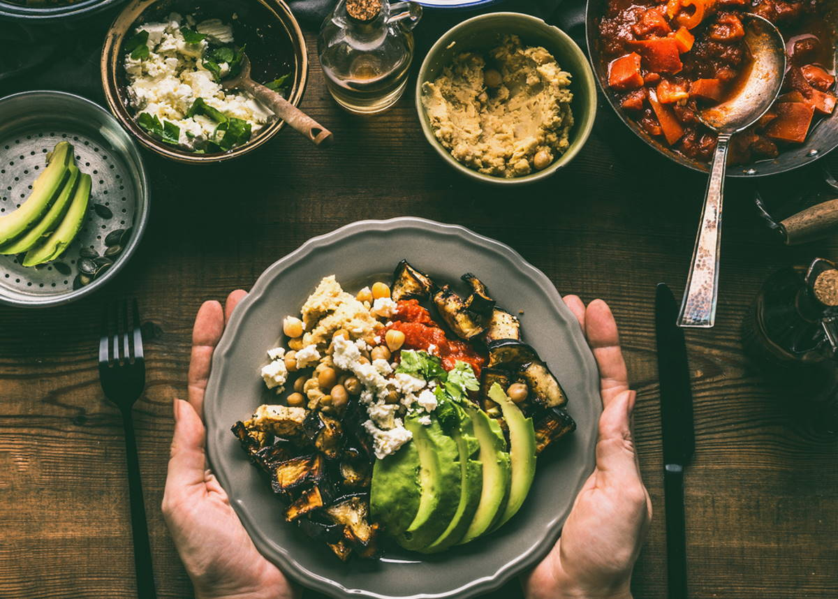 Female hands holding with healthy vegetarian bowl with various grilled vegetables, avocado and chickpea hummus on rustic background, top view. Clean food and dieting nutrition concept / snackconnection