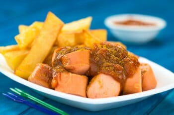 German fast food called Currywurst served with French fries on a disposable plate with party forks in the front (Selective Focus, Focus on the front of the sausage on top) / snackconnection