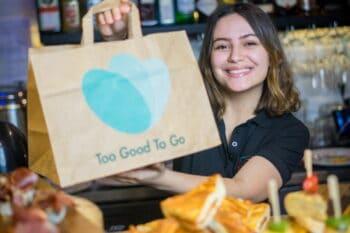 Frau aus der Gastronomie mit einer too good to go Papiertüte in der Hand / snackconnection