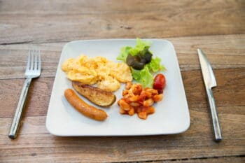 food, dinner and eating concept - scrambled eggs, sausage, chili beans and salad on plate / snackconnection