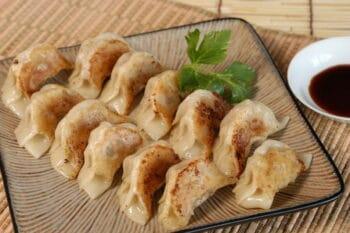 Gyoza gefüllte teigtaschen mit Fleisch oder Gemüse auf einem Teller / snackconnection