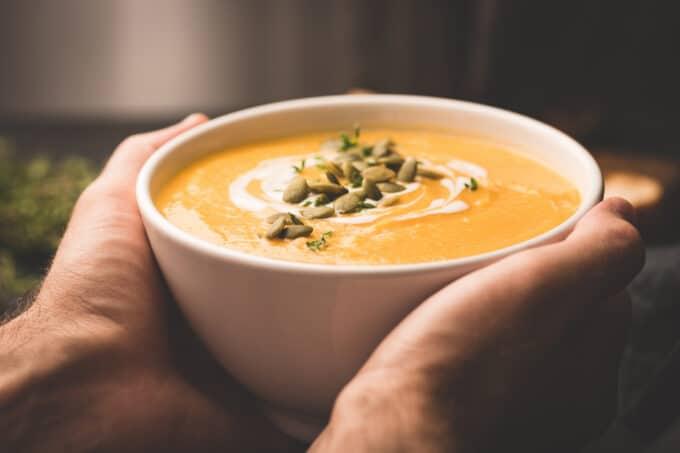 Kürbissuppe in Schüssel, zwei Hände halten Schüssel fest / snackconnection