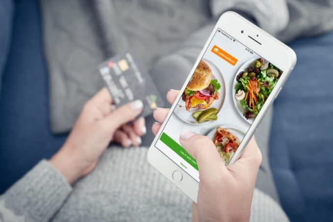 Smartphone mit geöffneter App von Lieferando und Kreditkarte im Hintergrund / snackconnection