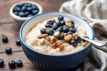 Oatmeal porridge with blueberries and almonds. Healthy breakfast porridge oats on a wooden table. Closeup view. Clean eating food