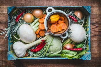 Organic local vegetables box for healthy clean eating and cooking on rustic wooden background, top view. Vegan or vegetarian food concept / snackconnection