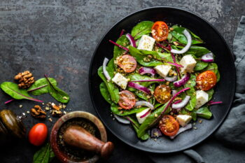 plate of nutritious simple salad with chard, walnuts, soft cheese, onions and oil, top view, space for text