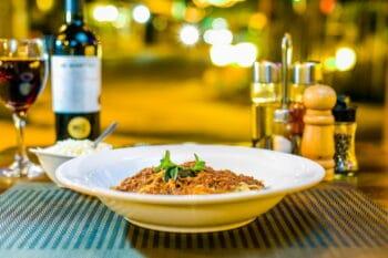 Spaghetti auf einem Teller im Restaurant, daneben Wein und Gewürze / snackconnection