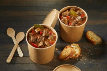 Two unlabelled takeaway tubs of rich beef goulash with spicy chili peppers served with toasted baguette and plastic spoons on a rustic wooden table with copyspace viewed high angle