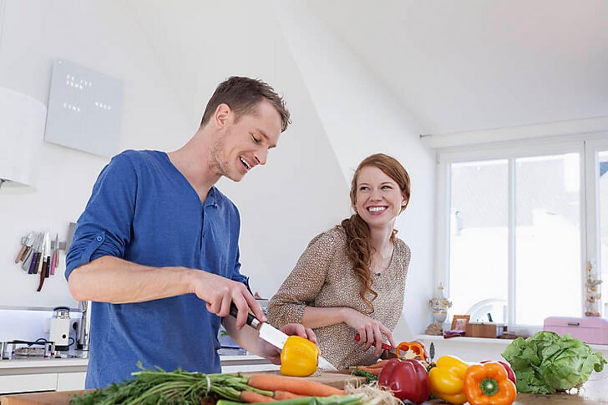 Zwei Menschen stehen in der Küche und lachen beim Gemüse schneiden / snackconnection