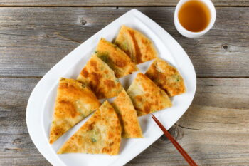 Top view of fried Asian pancakes with green tea and chopsticks on white plate. Rustic wooden boards underneath. / snackconnection