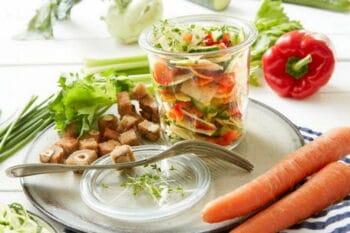 Rohkostsalat in einem Glas auf einem Teller mit Croutons / snackconnection
