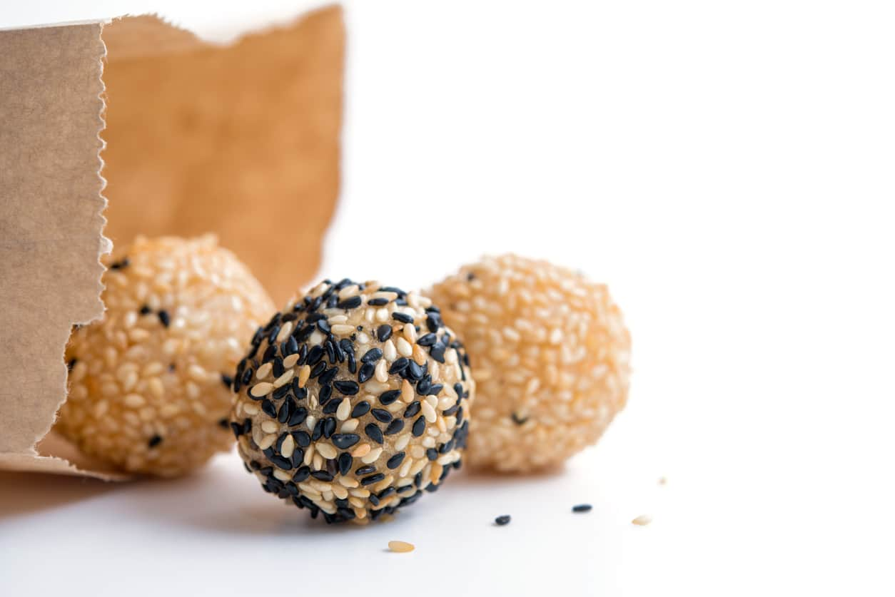 fried sesame dessert balls with paper bag on white background