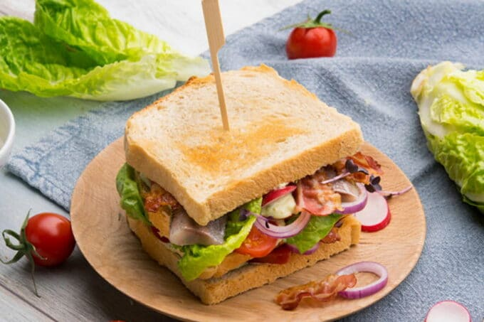 Club Sandwich mit Gemüse, Salat und Bacon / snackconnection