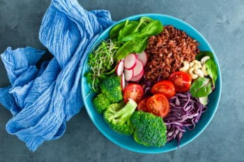 Buddha bowl meal with kale, spinach and chard leaves, brown rice, tomato, broccoli, radish, fresh green sprouts and pine nuts. Healthy balanced nutrition. Vegetarian food. Overhead view / snackconnection