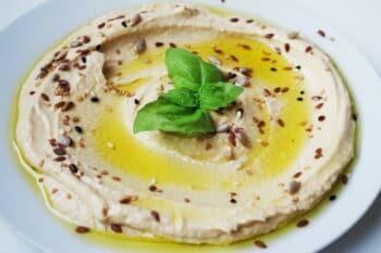 Hummus in einer Schüssel mit Olivenöl, sesam und Minze garniert / snackconnection
