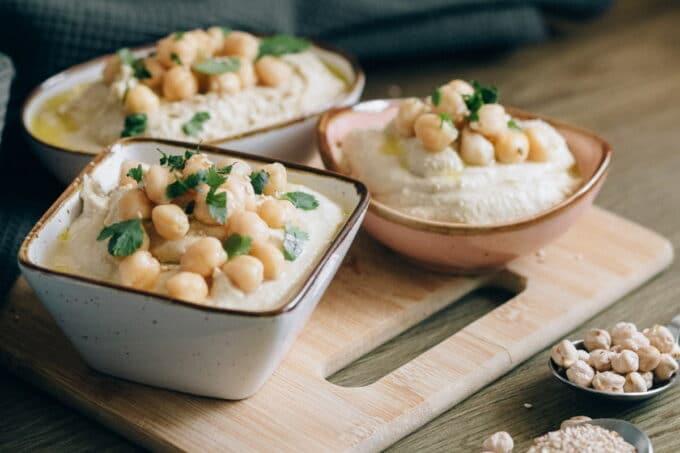 Hummus mit Kichererbsen in drei Schälchen auf einem Brett / snackconnection