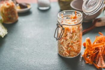 Simple fresh carrot cabbage salad in jars for healthy lunch is on kitchen table background, front view, with copy space. Vegetarian food, low-calorie vegetable eating and weight loss dieting concept / snackconnection