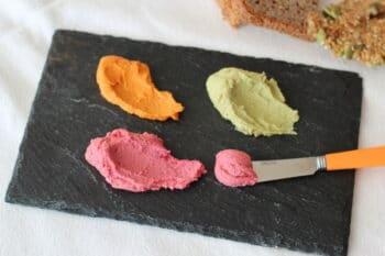 Verschiedene Sorten Hummus in rosa, weiß und orange auf einem Brett / snackconnection