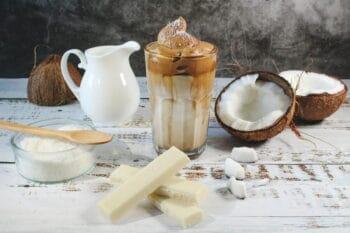 Whipped Kakao im Glas mit Milch und Kokosnuss im Hintergrund / snackconnection